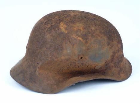 A Third Reich German Battle Damaged M35 Steel Helmet Shell, found at