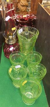 Lot 168 - A vaseline glass lemonade set of jug and five glasses, a cranberry glass jug, oil lamp with