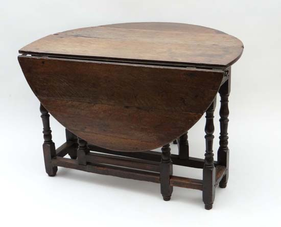An early 18thc oak oval gate leg table with drawer to one for 10 wide end table
